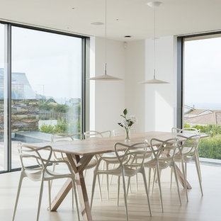 Large contemporary open plan dining room in Cornwall with concrete flooring, beige floors and white walls.