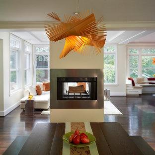 На фото: столовые в современном стиле с двусторонним камином и фасадом камина из металла