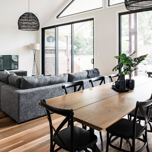 This is an example of a large contemporary open plan dining in Sydney with white walls and medium hardwood floors.