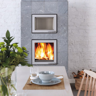 Large danish dining room photo in Gloucestershire with a wood stove