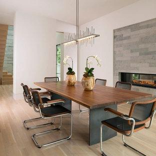 Modern inredning av en mellanstor separat matplats, med en dubbelsidig öppen spis, en spiselkrans i sten, vita väggar, ljust trägolv och beiget golv
