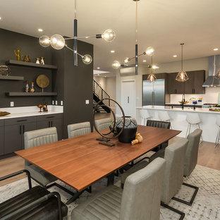 Esempio di una grande sala da pranzo aperta verso la cucina design con pareti nere e parquet chiaro