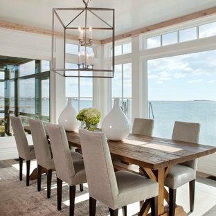 Example of a coastal beige floor dining room design in New York