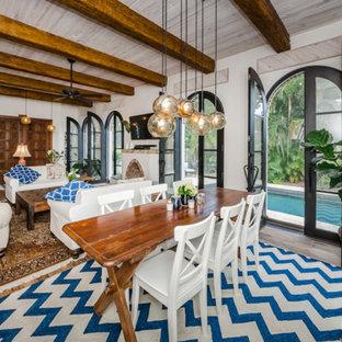 タンパの大きいエクレクティックスタイルのおしゃれなLDK (白い壁、無垢フローリング、茶色い床、薪ストーブ、漆喰の暖炉まわり) の写真