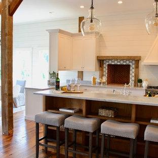 Esempio di una sala da pranzo aperta verso la cucina country di medie dimensioni con pareti bianche, pavimento in legno massello medio, stufa a legna, cornice del camino piastrellata e pavimento marrone