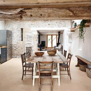 Ejemplo de comedor de cocina campestre, de tamaño medio, con paredes blancas y suelo naranja