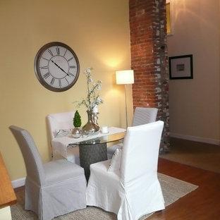 Idéer för att renovera en liten eklektisk separat matplats, med gula väggar och mellanmörkt trägolv