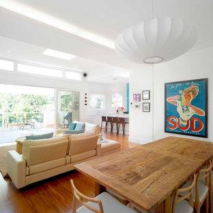 Ispirazione per una grande sala da pranzo aperta verso il soggiorno contemporanea con pareti bianche, pavimento in legno massello medio, nessun camino e pavimento marrone