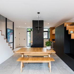Cette image montre une petite salle à manger nordique avec un sol en carrelage de porcelaine, un mur blanc et un sol gris.