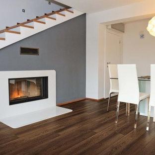 Cette photo montre une salle à manger ouverte sur la cuisine tendance de taille moyenne avec un sol en vinyl, un mur blanc, une cheminée standard, un manteau de cheminée en carrelage et un sol marron.