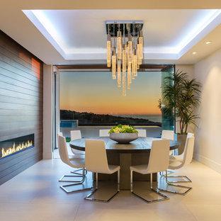 オレンジカウンティの広いコンテンポラリースタイルのおしゃれな独立型ダイニング (白い壁、横長型暖炉、木材の暖炉まわり、ベージュの床、コンクリートの床) の写真