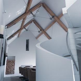 Idee per un'ampia sala da pranzo aperta verso il soggiorno contemporanea con pareti bianche, pavimento con piastrelle in ceramica, camino bifacciale, cornice del camino in pietra e pavimento bianco