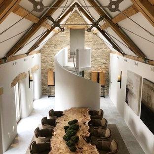 Ispirazione per un'ampia sala da pranzo aperta verso il soggiorno minimal con pareti bianche, pavimento con piastrelle in ceramica, camino bifacciale, cornice del camino in pietra e pavimento bianco