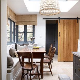 Foto di una piccola sala da pranzo aperta verso la cucina country con pareti bianche