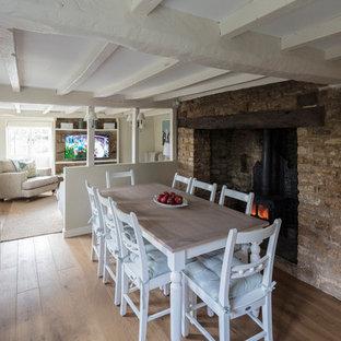 Foto di una piccola sala da pranzo country con pareti beige, pavimento in legno massello medio, stufa a legna e pavimento beige