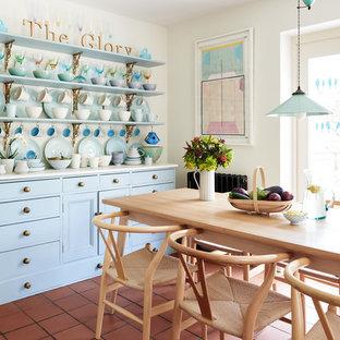 Idée de décoration pour une salle à manger champêtre de taille moyenne avec un mur blanc, un sol en carreau de terre cuite et un sol rouge.