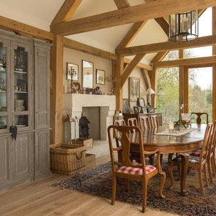 Diseño de comedor de estilo de casa de campo con paredes beige, estufa de leña y marco de chimenea de hormigón