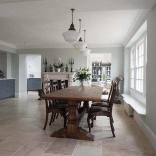 Lantlig inredning av ett stort kök med matplats, med grå väggar, kalkstensgolv, en standard öppen spis och en spiselkrans i sten