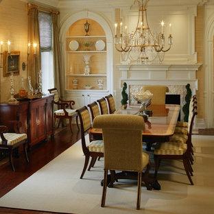 Immagine di una grande sala da pranzo classica chiusa con pareti gialle, pavimento in legno massello medio, camino classico e cornice del camino in pietra