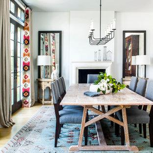 Cette photo montre une salle à manger chic avec un mur blanc, un sol en bois clair, une cheminée standard et un sol beige.