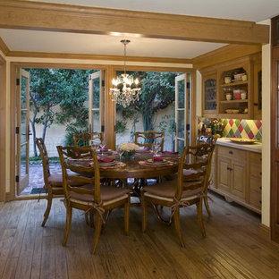 Modelo de comedor de cocina clásico, de tamaño medio, con paredes amarillas, suelo de madera en tonos medios y suelo marrón