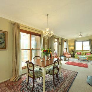 Foto di un'ampia sala da pranzo aperta verso il soggiorno country con pareti beige, moquette e stufa a legna