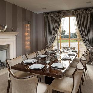 Immagine di una sala da pranzo classica con moquette, camino classico, cornice del camino in metallo e pareti marroni