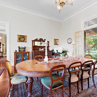 Traditional separate dining room in Sydney with white walls, medium hardwood floors, no fireplace and brown floor.