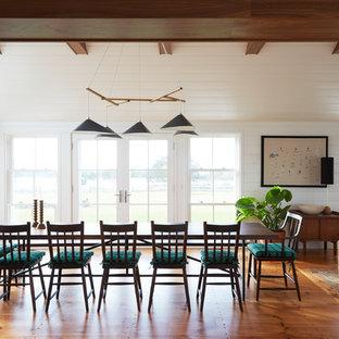 Cette photo montre une salle à manger bord de mer avec un mur blanc, un sol en bois brun et cheminée suspendue.
