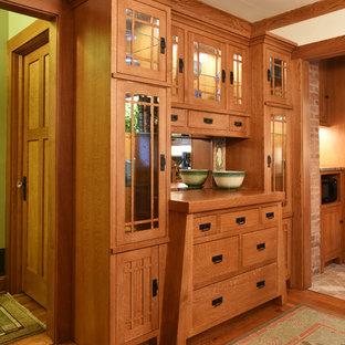 Cette photo montre une petite salle à manger craftsman avec un mur beige et un sol en bois brun.