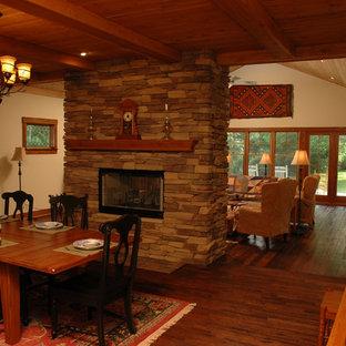 Immagine di una sala da pranzo aperta verso il soggiorno american style di medie dimensioni con pareti beige, pavimento in legno massello medio, camino bifacciale e cornice del camino in pietra