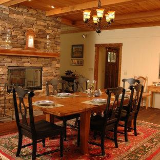 Modelo de comedor de estilo americano, de tamaño medio, abierto, con paredes beige, suelo de madera en tonos medios, chimenea de doble cara y marco de chimenea de piedra