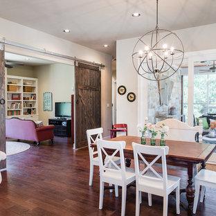 Immagine di una sala da pranzo aperta verso la cucina american style con pareti beige, pavimento in legno massello medio e nessun camino