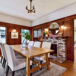 Cette photo montre une salle à manger craftsman en bois fermée avec un mur blanc, un sol en bois brun, une cheminée standard, un manteau de cheminée en brique et un sol marron.
