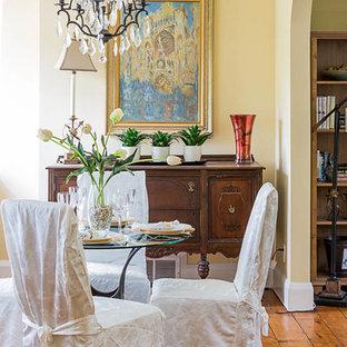 Ejemplo de comedor tradicional, de tamaño medio, abierto, con paredes amarillas, suelo de madera en tonos medios, chimenea tradicional y marco de chimenea de hormigón