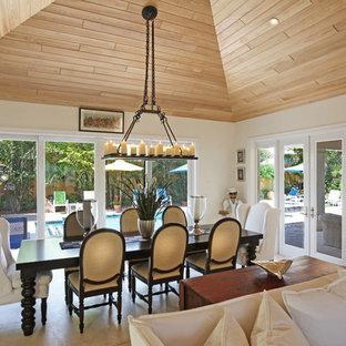 Ispirazione per una sala da pranzo aperta verso la cucina tropicale di medie dimensioni con pareti bianche, pavimento in travertino e nessun camino