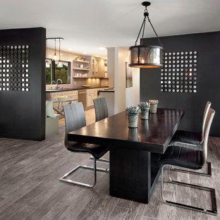 Immagine di una grande sala da pranzo aperta verso la cucina minimal con pareti nere e pavimento in legno massello medio