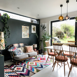 Design ideas for a medium sized bohemian open plan dining room in London with concrete flooring and white floors.