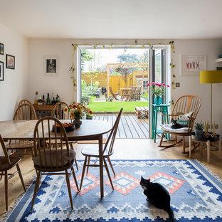 Bild på en liten minimalistisk matplats, med vita väggar, ljust trägolv, en standard öppen spis och brunt golv
