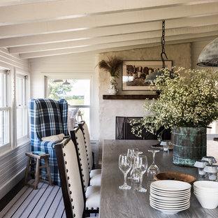 Ejemplo de comedor campestre, grande, abierto, con paredes blancas, suelo de madera oscura, chimenea tradicional, marco de chimenea de hormigón y suelo marrón