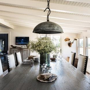 Diseño de comedor de estilo de casa de campo, grande, abierto, con paredes blancas, suelo de madera oscura, suelo marrón, chimenea tradicional y marco de chimenea de hormigón