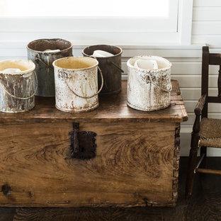 Ejemplo de comedor de estilo de casa de campo, grande, abierto, con paredes blancas, suelo de madera oscura, chimenea tradicional, marco de chimenea de hormigón y suelo marrón