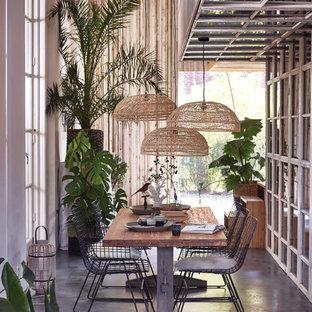 Idee per una grande sala da pranzo tropicale con pavimento in cemento