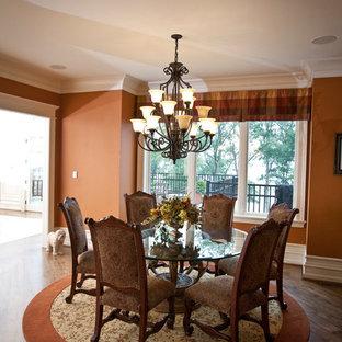 Ispirazione per un'ampia sala da pranzo aperta verso la cucina tradizionale con pareti arancioni e parquet scuro