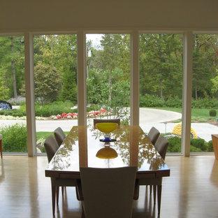 Exemple d'une salle à manger ouverte sur le salon moderne de taille moyenne avec un mur blanc, un sol en bois clair et aucune cheminée.