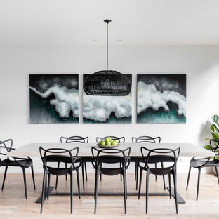 This is an example of a mid-sized modern kitchen/dining combo in Sydney with white walls and light hardwood floors.
