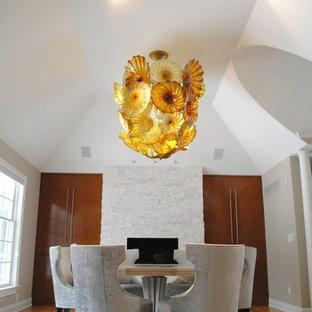 Aménagement d'une grand salle à manger classique fermée avec un mur blanc, un sol en bois clair, cheminée suspendue et un manteau de cheminée en pierre.