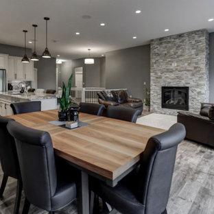 Foto di un'ampia sala da pranzo aperta verso la cucina american style con pareti grigie, pavimento in laminato, camino lineare Ribbon, cornice del camino in pietra e pavimento marrone
