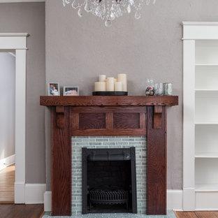 Immagine di una piccola sala da pranzo aperta verso la cucina stile americano con pareti grigie, parquet chiaro, camino classico e cornice del camino piastrellata