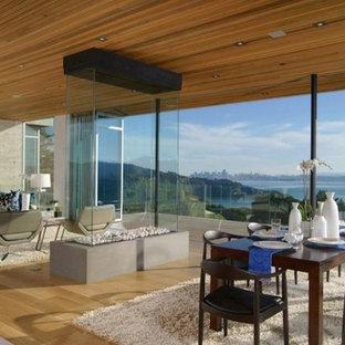 Свежая идея для дизайна: огромная столовая в современном стиле с бежевыми стенами, полом из известняка, двусторонним камином и фасадом камина из камня - отличное фото интерьера